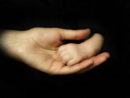 Ein Hand einer Mutter hält die Hand eines Babys