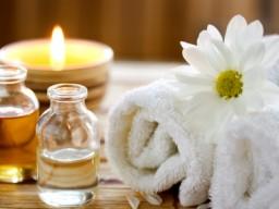 Ölgläschen und ein mit Blumen verziertes Handtuch im Kerzenschein