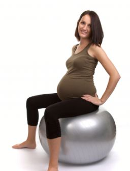 Eine schwangere Frau auf einem Gymnastikball