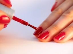 Frau lackiert sich Nägel rot