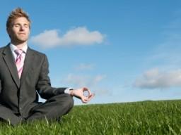 Geschäftsmann beim Yoga auf der Wiese