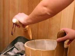 Wasserbehälter und heißer Steinofen in der Sauna