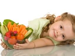 Kleines Mädchen mit einer Schüssel voll Gemüse
